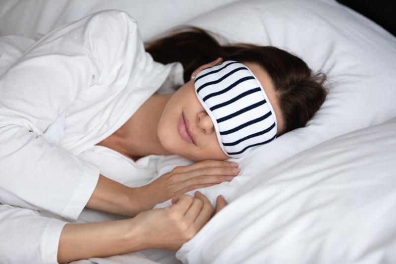 woman sleeping happily with eye mask