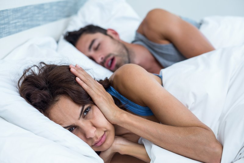 woman in bed next to snoring man