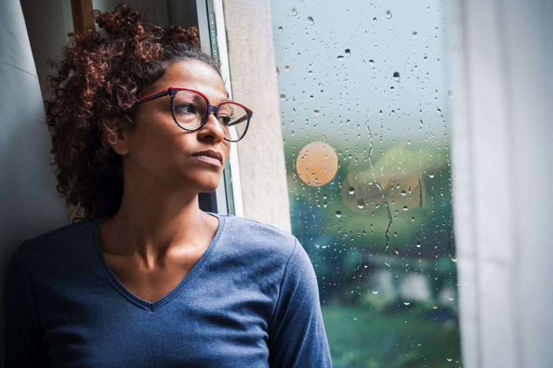 depressed woman looking out a rainy window