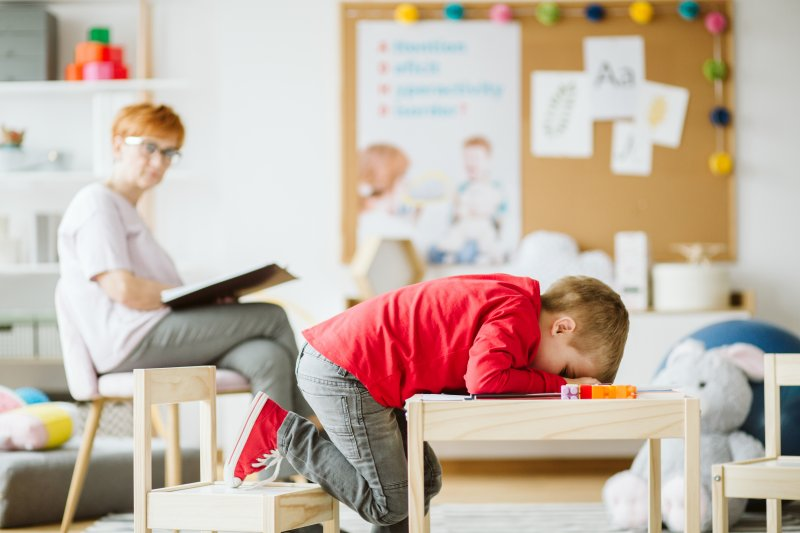 young child sleep at desk in school