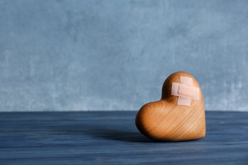 a wooden heart with a band-aid on it