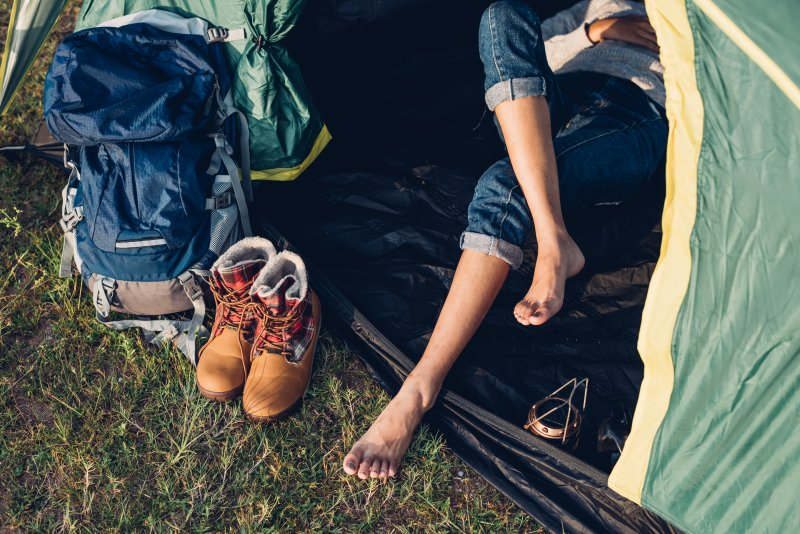 young woman sleeping outdoors in tent