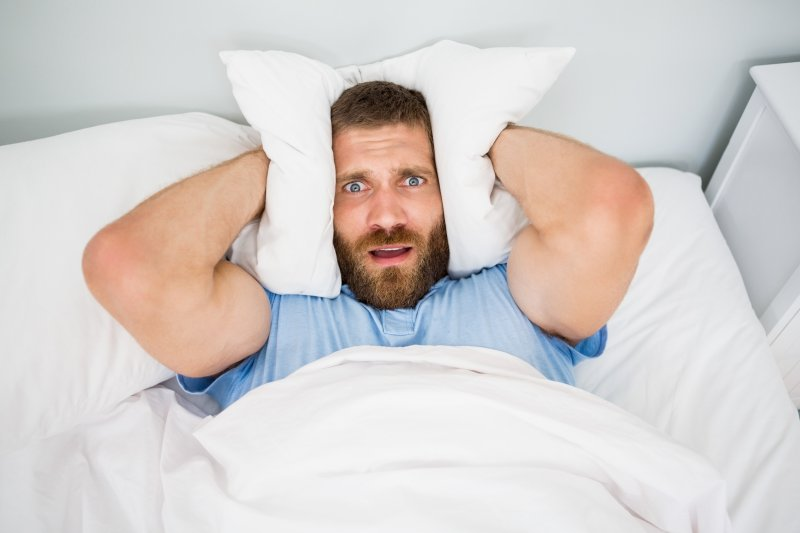 man covering ears in bed