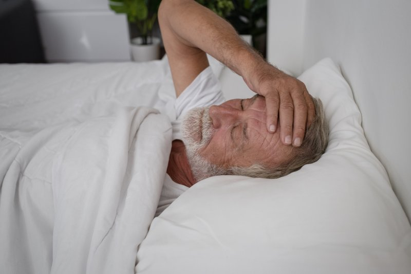 older man laying in bed